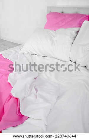 Crumpled pink linen on bed - stock photo