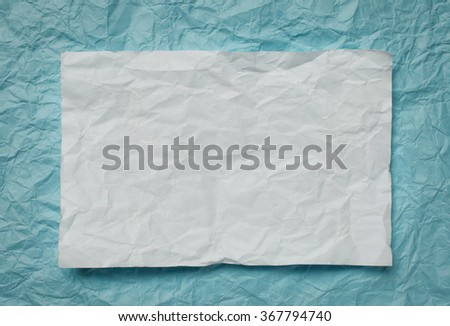 Crumpled  white paper card on cyan  background, place for tex