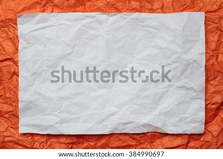 Crumpled  white paper card on orange background, place for tex
