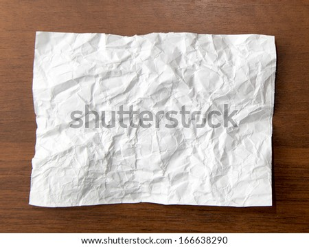 crumpled white paper on the wooden background