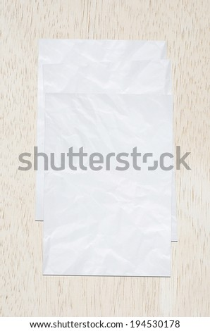 Crumpled white papers on wood board.