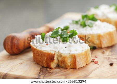 crunchy baguette slices with cream cheese and green onion on olive board - stock photo