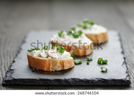 crunchy baguette slices with cream cheese and green onion on slate board - stock photo