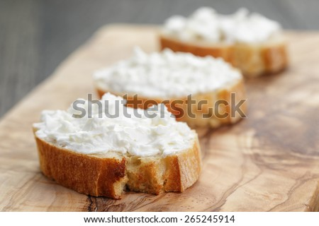 crunchy baguette slices with cream cheese on olive board - stock photo