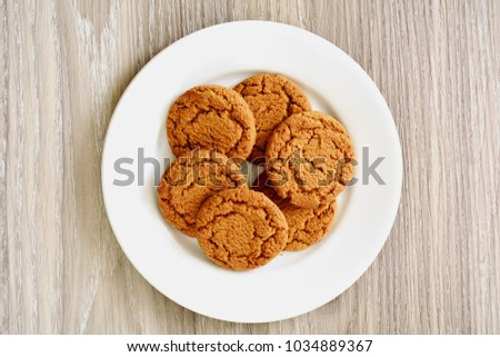 Crunchy gingersnaps on white plate from overhead on textured wooden background