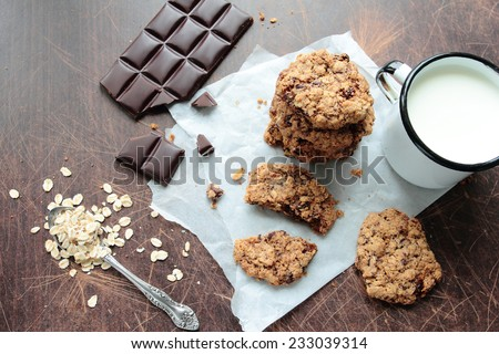 Crunchy oat cookies with dark chocolate and mug of fresh milk - stock photo