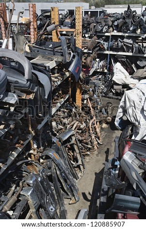 Crushed and damaged car parts at junkyard