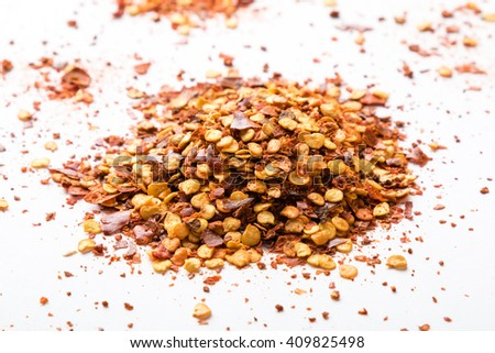 crushed dried chili flakes on white table - stock photo