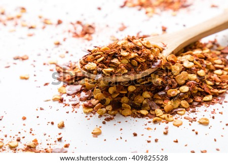 crushed dried chili flakes on white table with spoon - stock photo