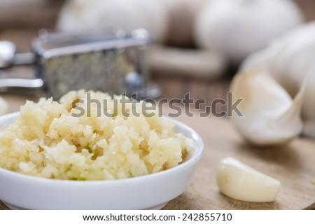 Crushed Garlic (close-up shot) on rustic wooden background - stock photo