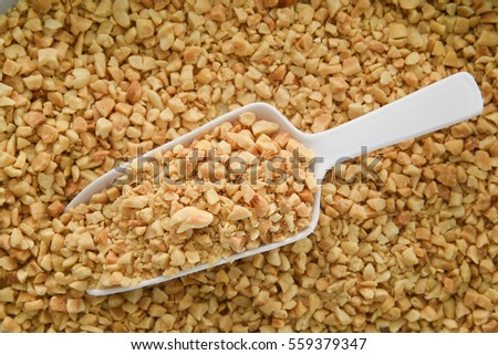 Crushed or chopped peanuts with a white plastic scoop