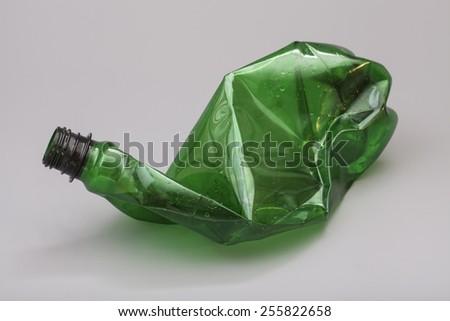 Crushed plastic bottle isolated on gray background - stock photo