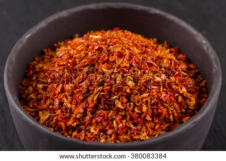 Crushed red chili pepper in stone bowl on dark background - stock photo