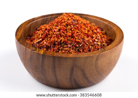 Crushed red chili pepper in wooden bowl on white background - stock photo