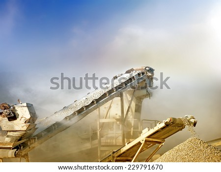 Crushing stones for gravel production on mining quarry - stock photo
