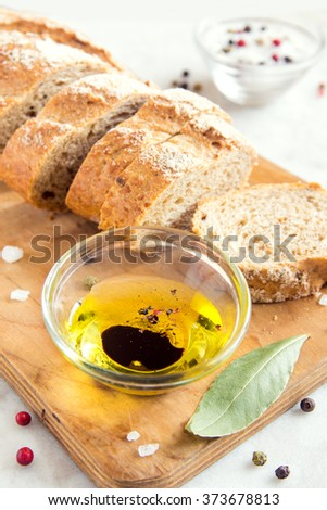 Crusty bread ciabatta and bowl of olive oil with balsamic vinegar, sea salt and spices close up