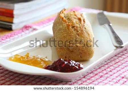 Crusty bread roll served with preserves - stock photo