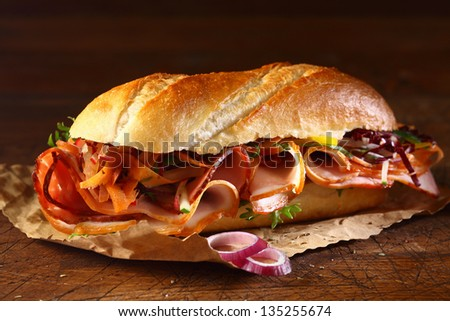 Crusty crisp golden baguette with a ham and onion filling on a small piece of grungy brown paper on a wooden table top - stock photo