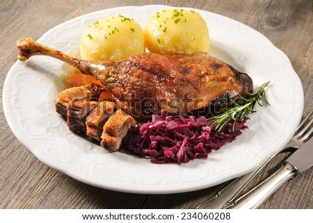 Crusty goose leg with braised red cabbage and dumplings - stock photo