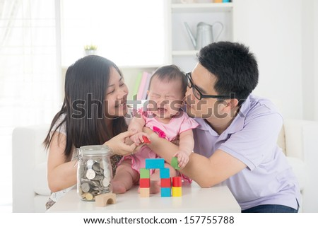 crying asian baby being comforted by chinese parents - stock photo
