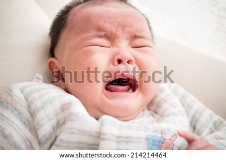 crying asian newborn baby lying on bed - stock photo