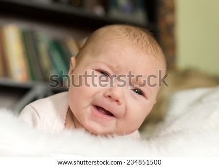 Crying baby boy, baby lying on his stomach and crying - stock photo