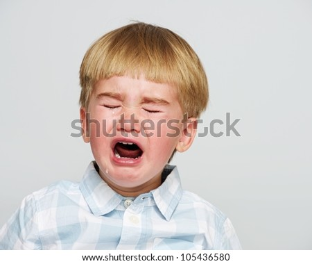 Crying baby boy in checkered shirt - stock photo