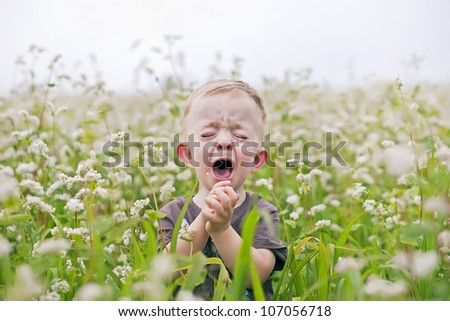 crying baby boy on the field - stock photo