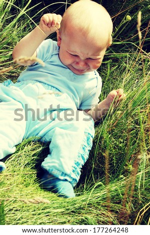Crying baby boy outdoors at sunny summer day  - stock photo