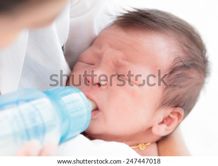 Crying baby eating - stock photo