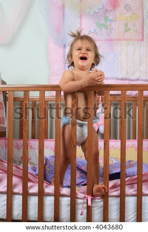 Crying baby girl wanting out of her crib - stock photo