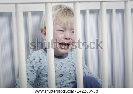 crying baby in bed - stock photo