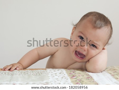 Crying baby or toddler child, boy or girl, at home leaning on bed.