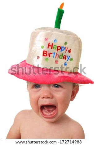 Crying baby wearing a Happy Birthday hat. - stock photo
