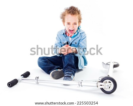 Crying boy with wounded leg near by scooter - stock photo