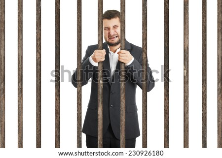 crying businessman behind the prison cell over white background - stock photo