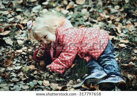 crying child in autumn leaves, autumn depression and sadness - stock photo