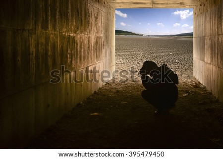 Crying child in tunnel and dry cracked ground - stock photo