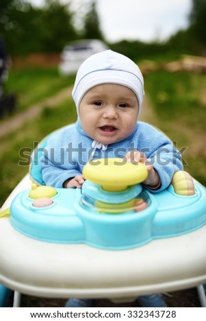 Crying cute baby in baby walker walks outdoors - stock photo