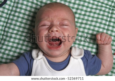 Crying eight week old newborn baby boy on a green play mat - stock photo