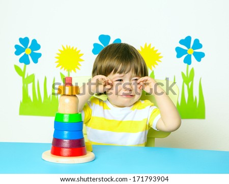 Crying, frustrated baby boy with tears In kindergarten or day care.  - stock photo