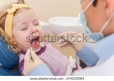 crying girl at dentist opened mouth. man dentists examining one girl in dentist chair - stock photo