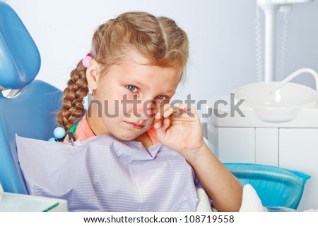 Crying girl in the dentist seat - stock photo
