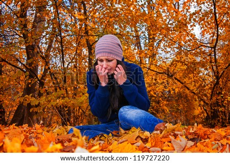 crying girl on the fallen leaves - stock photo