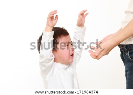 crying Japanese little boy who is being held by her mother - stock photo