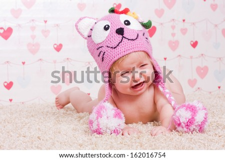 Crying little baby with pink hat lies down on his stomach - stock photo