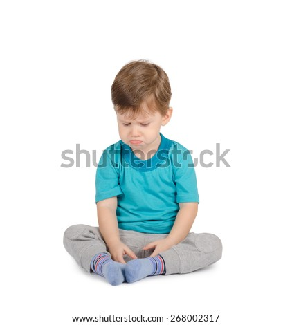 Crying little boy sitting on the floor isolated on white background