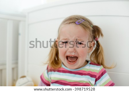 Crying little toddler, having a tantrum during a terrible two phase, raging in her crib. Childhood, growing up, developmental phase and parent patience concept.  - stock photo