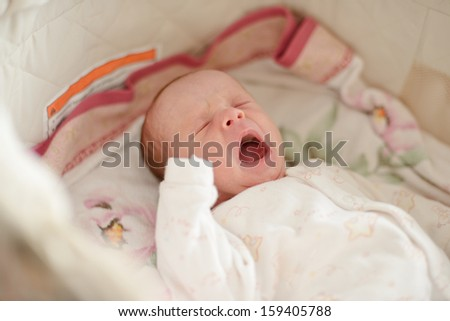 crying newborn is laying in crib - stock photo