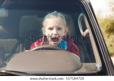 Crying scared girl driving the car - stock photo